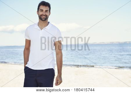 Casual guy on beach smiling to camera