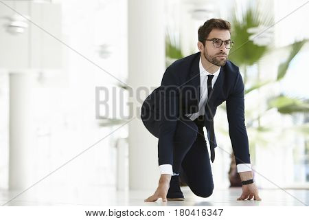 Determined to win businessman crouching in suit and tie