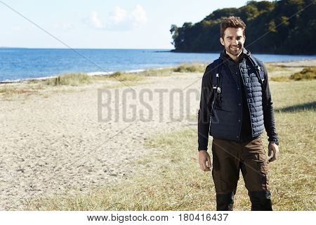 Happy hiker standing on beach smiling at camera