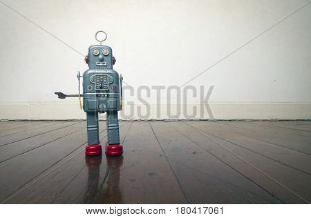 vintage robot toy standing on a wooden floor with copy space