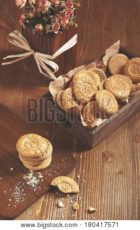 Top view of cookies in the box and dry roses on wooden board. Biscuits stack and one broken cookie with crumbs on cutting board.