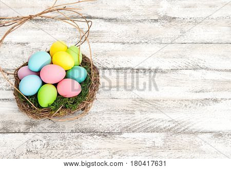 Easter eggs in nest on rustic wooden background. Easter decoration. Vibrant colors