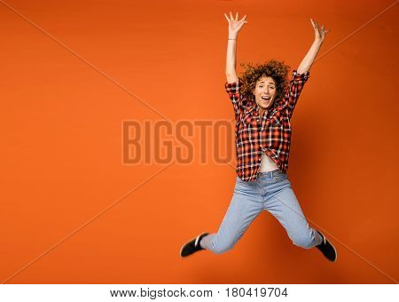 Young Natural Curly Woman Standing Over An Orange Background Being Very Excited And Jumping