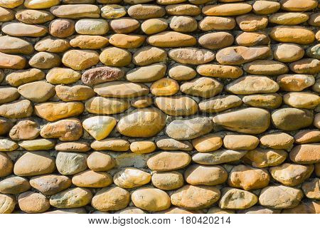 River pebbles round stone wall background in sunshine