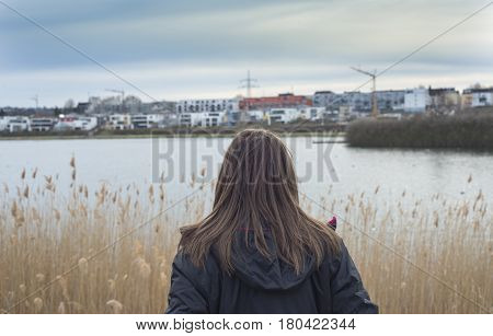 Woman on the lake looking at a new neighborhood of luxurious and exclusivist houses