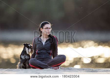Young pretty woman sitting on river coast with her dog miniature schnauzer