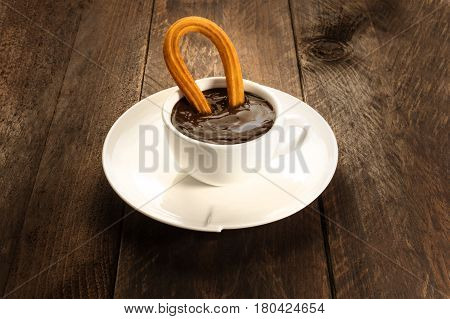 A photo of a churro, traditional Spanish, and especially Madrid, dessert, particularly for Sunday breakfast, dipped into hot chocolate. With a place for text