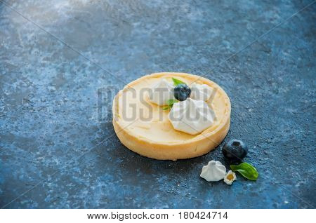 Individual Lemon Curd Tarts With Blueberry Jam Meringue Basil Leaves On A Blue Rusty Background. Fla