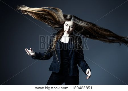 Vogue shot. Portrait of a fashionable model with beautiful long hair posing at studio in a motion. Haircare, hairstyle concept.