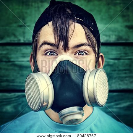 Toned Photo of Teenager in the Gas Mask on the Wooden Wall Background