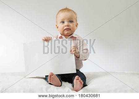 Baby boy holding white blank. Infant kid sitting with poster in his hands. Mock up. Copy space. Idea for postcard.