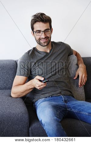 Guy with emote control on sofa smiling
