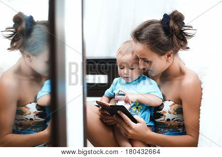 A mother and her child look at the phone on the floor in light bedroom