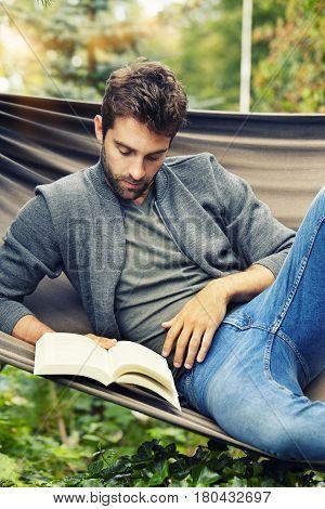 Man reading book on hammock in garden