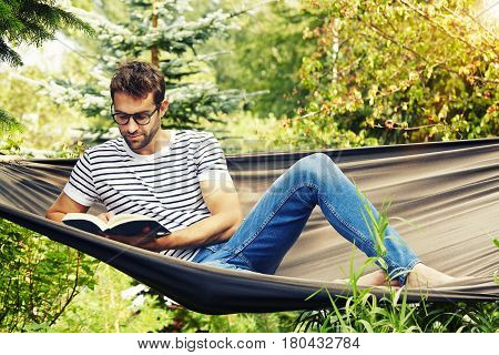 Dude reading and relaxing on hammock in garden
