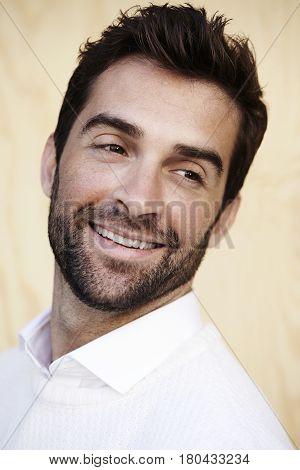 Stubble man smiling close up studio shot