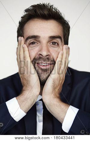 Businessman pulling face at camera studio shot