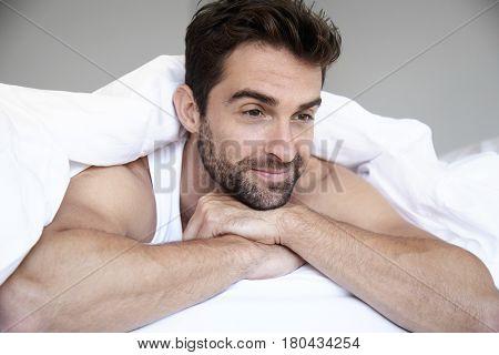 Man lying in bed under duvet in bedroom