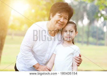 Portrait of beautiful multi generations Asian family at nature park. Grandmother and granddaughter at outdoor. Morning sun flare background.