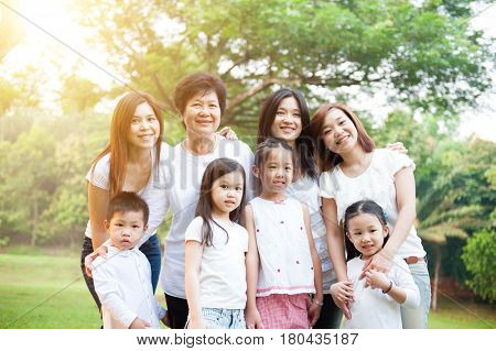 Group of happy Asian multi generations family portrait, grandparent, parent and children, outdoor nature park in morning with sun flare.