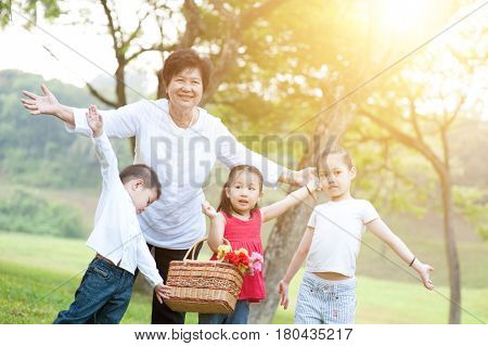 Portrait of beautiful multi generations Asian family at nature park. Grandmother and grandchildren having fun at outdoor. Morning sun flare background.