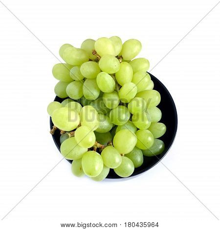 Lot of ripe green grape berries on bunch in black round bowl on white background top view close up