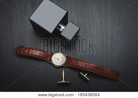 Perfume with belt and cuff in black background
