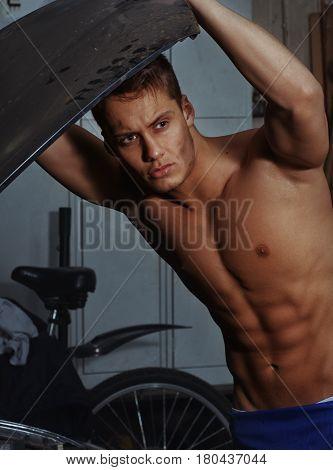 Sexy mechanical man lifted the car's hood.