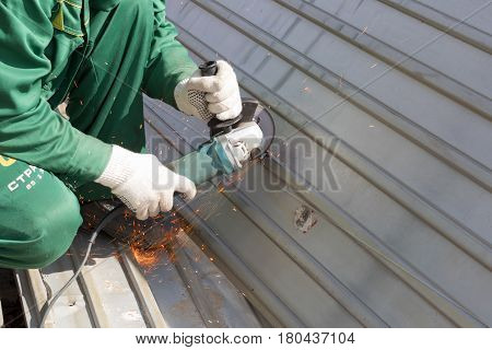 worker in green uniform and in rags gloves grinds corrugated steel structure for painting primer anti rust. Red sparks from wheel.