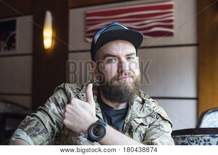 A bearded guy. The guy shows the class. A man in a khaki jacket in a baseball cap. The guy with the watch on his arm. Cheerful bearded guy