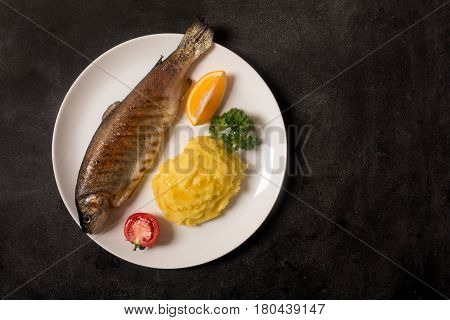 Grilled whole trout, mashed potato, lemon and parsley, top view. Dark chalkboard