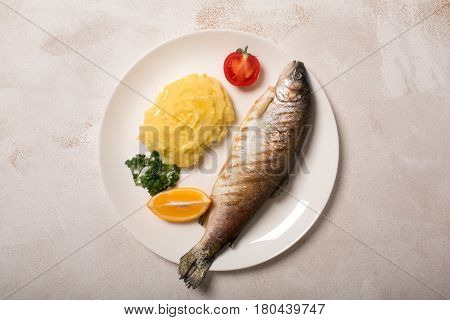 Grilled whole trout, mashed potato, lemon and parsley, top view. White background