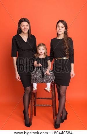 Two beautiful young girls in business suits and a little girl in a black dress on a red background in the studio