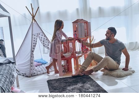 Carefree time together. Father and daughter playing with a dollhouse together while sitting on the floor in bedroom