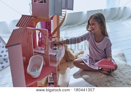 Using fantasy to play. Cute little girl playing with a dollhouse while sitting on the floor in bedroom