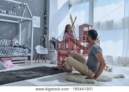 Using imagination. Father and daughter playing with a dollhouse together while sitting on the floor in bedroom