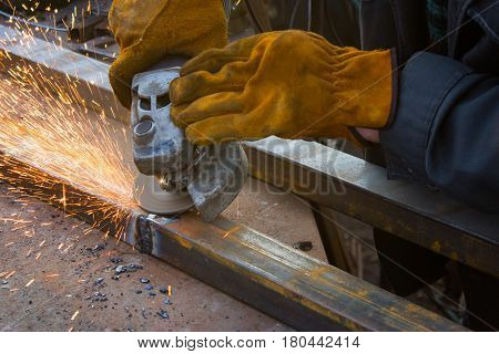 Cutting metal with grinder. Sparks while grinding iron. Man in yellow gloves poster