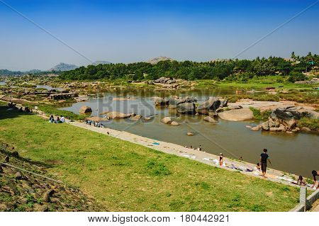 Hampi, India - November 20, 2012: Indian people in traditional clothes relax on the shore of Tungabhadra River and dry their things. Crossing the Hampi's river