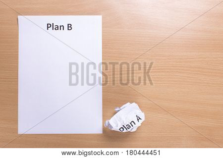 Crumpled paper Plan A and clean sheet Plan B on a wood  background