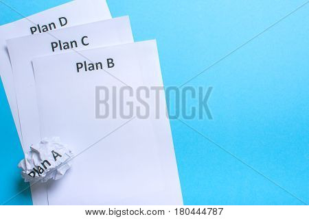 Crumpled paper Plan A and clean sheet Plan B C D on a blue background
