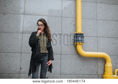 Fashion Consept: Beatiful Young Girl With Long Hair, Glasses, Red Lips Standing Near Modern Wall Wea