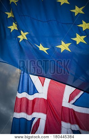 Brexit flags of Europe and Uk overlapping against moody sky