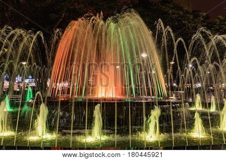 Colored fountain at might in circle inn Hai Phong Vietnam. Brightly and colorfully lit fountain