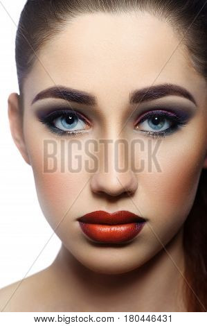 Vertical cropped close up shot of a beautiful red lipped blue eyed young woman wearing professional makeup with smoky eyes isolated beauty fashion red lips blue eyes cosmetics style model skin concept.