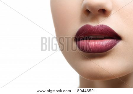 Cropped close up of a sexy sensual mouth of a gorgeous woman with full lips covered in purple lipstick isolated on white copyspace cosmetics makeup style fashion beauty skincare augmentation concept.