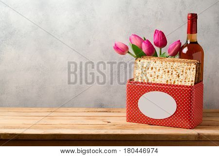Passover celebration concept with matzoh wine and tulip flowers over bright background with copy space