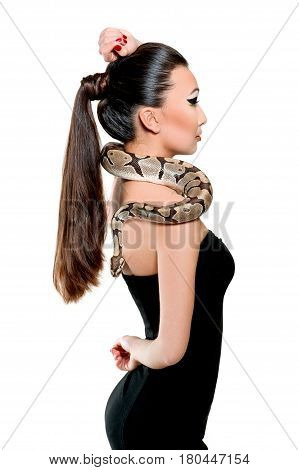 Profile studio shot of a beautiful Asian woman with her hair in a ponytail wearing classic black dress holding a python on her shoulders isolated on white elegance exotic extreme beauty fashion style.