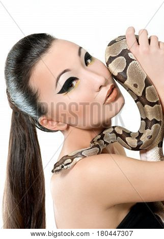 Young sexy dark haired Asian girl with evening makeup holding a snake posing sensually looking to the camera seductively beauty fashion exotic reptile animal nature cosmetics skin product concept.
