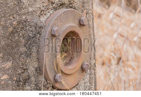 Closeup of large iron flange bolted onto a metal container sealed in concrete with blurred background of tall grass