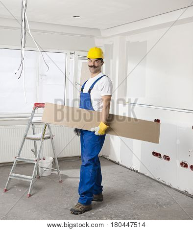 Construction worker wearing overalls and helmet carrying piece of wood.